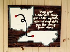 """$100 - Two states, hand-painted, wooden sign. """"May your adventures bring you closer together, even as they take you far away from home."""" The sign pictured is 30"""" wide by 24"""" tall. Dark Walnut stain on pine wood. Sign comes ready to hang with hanging wire. Made to order - customization of states and colors available - allow 2-3 weeks turn around time. Back of sign is unfinished wood. Due to the nature of wooden products, the coloring, knots, and imperfections can vary slightly from photo."""
