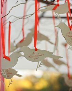 Guests at this wedding will find their names and table assignments on calligraphed die-cut birds tied to branches.