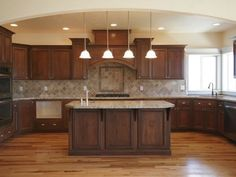 wood floor, dark cabinets, lighter tan or brown counter by lena