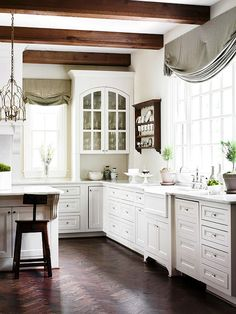 Herringbone-pattern wood floors and dark wood ceiling beams add vintage appeal to this white kitchen. The arched, glass-front upper cabinets and recessed toe-kicks further emphasize the vintage vibe.