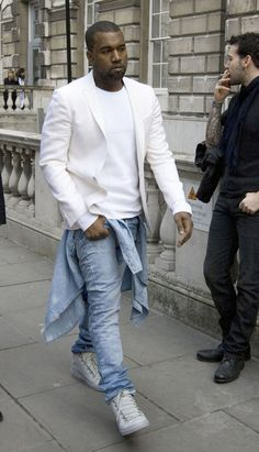 Mr. West at london fashion week rocking that Balmain light blue denim shirt around his waist, with a white pair of wrinkled leather Balenciaga Arena sneakers, and a white blazer layered with a white crewneck!    As Kanye raps:  I get it custom, you a customer You ain't 'customed to going through Customs, you ain't been nowhere, huh?