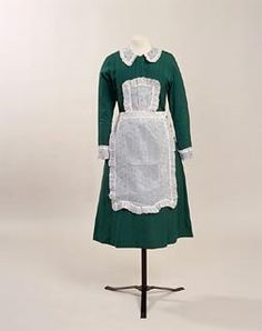 1933-1937; Parlor maid's dress & uniform.  Dress of dark green rayon with cap, apron, collar and cuffs of embroidered stiffened white muslin. Dress fronts cut in one section; fastens from waist to high v-neck with five press studs under central fold of fabric with eleven small self-fabric buttons; calf-length skirt cut in two sections. Cap, cuffs, collar and apron of stiffened white muslin, embroidered with mauve silk in small-scale design of flowers and spots, frills edged with mauve silk.