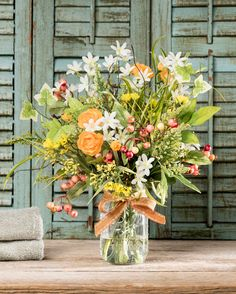 Bring the freshness of a country meadow into your cozy nook with wildflowers arranged in a pint mason jar of our clear acrylic water. Vibrant orange ranunculus, coral berries, and yellow statice, balanced with soothing white rock cress and mixed greenery, provide warming natural beauty in a happy combination of color.