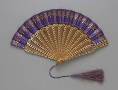 1867-1876, America - Fan manufactured by Edmund Soper Hunt Fan Factory - Silk satin leaf decorated with brass sequins and spangles; carved wood sticks covered with gold leaf; mother-of-pearl; silk tassel