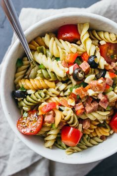 Best easy pasta salad recipe served in white bowl with sliced grape tomatoes