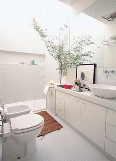 O espaço exíguo de 4,50 m² tem a área de banho delimitada pela abertura no teto, por onde entra luz. Um vidro fixo cumpre o papel de evitar respingos. O nicho feito na alvenaria (75 cm de largura) guarda os produtos de higiene. Projeto de Roberto Negrete.