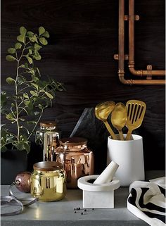 counter chic. Trio of copper, silver and gold stainless steel canisters stash edibles in opulence. Perfectly sized for coffee, tea, nuts, dog treats—you name it. Capped of with rich rounds of mango wood, notched for easy opening.