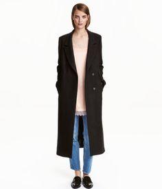 Zwart. Een lange jas van wolmix met revers en een blinde, dubbele knoopsluiting voor. De jas heeft zakken met klep voor, paspelsteekzakken, een binnenzak