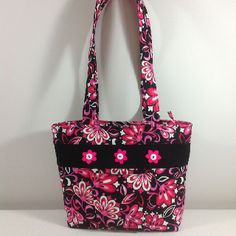 """This floral, quilted purse is the perfect summer accessory!  Complete with front pocket, zip enclosure, eight credit card slots, cell phone pocket and nine other various sized pockets for pens, money, glasses, etc.    Machine washable.  Approximately 14"""" wide x 10"""" tall x 5.5"""" deep.   This purse is custom made by myself.  More images are available upon request.    Available in more patterns and various colors.  For more information or purchasing requests, please email Laura at…"""