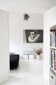 Valkoisen olohuoneen katseenkiinnittäjät: taulu, valaisin ja pinkki maljakko