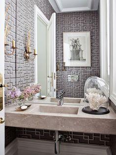 Aseo con paredes empapeladas y lavabo encastrado en encimera