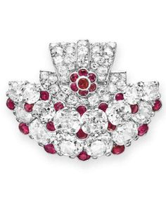 AN ART DECO DIAMOND AND RUBY CLIP BROOCH, BY CARTIER. Designed as an old mine-cut and circular-cut diamond plaque, enhanced by collet-set ruby detail, mounted in platinum, circa 1925, signed Cartier, Paris, numbered. #Cartier #ArtDeco #brooch