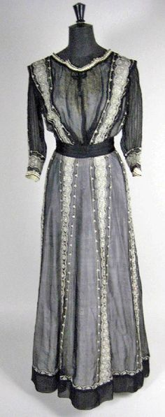 Afternoon dress, ca.1912. Black silk chiffon over fine ivory silk taffeta, the chiffon with ivory lace vertical insertions to skirt and bodice. One piece. Brightwells