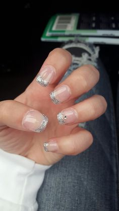 clear manicure with intense silver glitter and a rhinestone accent on the ring fingernail