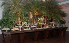 para contrastar com a entrada a mesa de doces era suave e cheio de arvores e muito verde