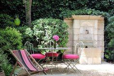 A Saint-Rémy-de-Provence, dans la cour de La Maison de Village, une table en fer forgé et ses chaises assorties côtoient un transat pour un instant de détente auprès de la fontaine en pierre et de la végétation luxuriante. Côté couleur, le rose fuchsia des galettes de chaises et de la toile du transat tranche avec la verdure environnante. ❤