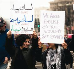 "(left sign reads, ""Not Saints, Not Whores, Just Women"" in both english and arabic)   Right sign reads, ""We added English so you wouldn't get scared."""