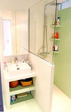 Petit plan vasque construit sur mesure en aggloméré marine et carrelé qui s'appuie sur le muret cloison de la douche