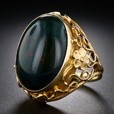 A deep green cabochon bloodstone with cinnabar speckles is presented in a lush and lovely gold mounting ornamented with flowers, leaves and flowing tendrils