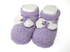 Schöne Babyschuhe aus weicher Merinowolle (Schurwolle) in flieder, verziert mit einer gehäkelten Schleife und einer Satinrose. Geschlossen werden ...