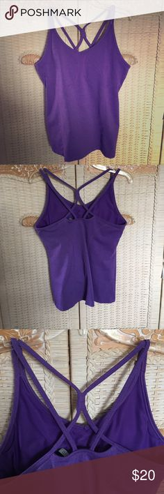 Athleta workout top with built in shelf bra This workout top by Athleta is very comfortable and has a built-in shelf bra with padding that can come out if you wish to have a more natural look. Good quality stretch nylon, polyester, and Lycra. Criss-cross back design. Athleta Tops Tank Tops