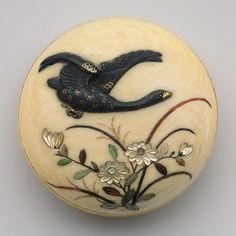 Netsuke: Goose and swallow, 19th century Japanese ~  Ivory, metal alloy, mother-of-pearl, tortoiseshell ~ On the obverse of this manju-shaped netsuke, a goose of gold and copper alloy hovers over chrysanthemums and other autumn grasses of inlaid mother-of-pearl and tortoiseshell. On the reverse, similar materials are arranged to render a swallow as it gazes above at hanging wisteria. Seasonal motifs are a favored theme in Japanese art.