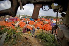 Tent city in Mogadishu, Somalia.  Note the gun above.