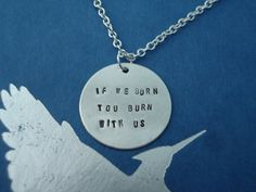 "The Hunger Games  -  ""If We Burn You Burn With Us""  Hand Stamped Silver  Necklace  -  Mockingjay. $17.99, via Etsy."