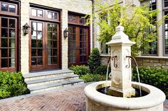 English Tudor style in Dallas. Fusch Architects. i love those wooden doors. the lamps are cool. the pattern in the brickwork on the patio is lovely. the fountain is cool too. the stairs are really well done. i would LOVE to have this as my patio.