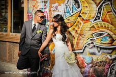 Filipino wedding photography in winnipeg by Vancouver wedding photographer Trevor Brucki.  Heart shaped hands with bride and groom, graffiti wall in exchange district, downtown winnipeg, manitoba.