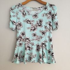Love by design top Light teal color with black and white flower pattern. Short sleeve with slight puff at shoulder. Excellent condition! Skirted top. Love by design Tops Tees - Short Sleeve