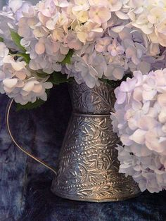Pastel Hydrangeas in pitcher - close-up These lovely hydrangeas began as white flowers and turn colors as they age. The containers are embossed brass with a silver finish. The backdrop was a mottled blue velour. Photographed with available light.