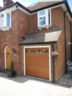 Hormann S-Panel sectional garage door with windows in golden oak decograin