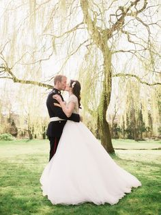 John Barwood Photography - Allure Bridal gown for a Classic Spring Wedding at Eastington Park Gloucestershire with Blossom Floral Display, Pastel Bouquets and Groom in Military Uniform.