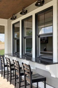 Three vintage barn sconces are mounted to gray siding over black framed windows . Three vintage barn sconces are mounted to gray siding over black framed windows positioned above a black granite bar seating black ladder back barstoo. Kitchen Window Bar, Patio Kitchen, Kitchen Windows, Patio Windows, Kitchen Seating, Room Kitchen, Farmhouse Windows, Granite Kitchen, Deck Kitchen Ideas