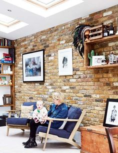 mel walker and otis sitting infront of a stripped back brick wall in industrial kitchen extension