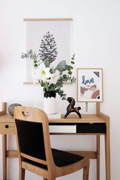 Beautiful wooden desk and chair with black details. If you are one of those who works from home irregularly, decorate your work space with some flowers in the meanwhile! The pine cone print and needlepoint work either way, cheering up your home office interior.  Via Seelected