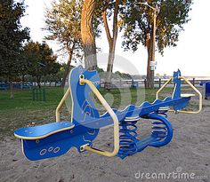 A two-dinosaur teeter-totter on the playground near the beach.