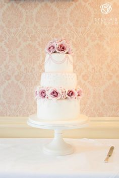 www.sylviaskitchen.co.uk Three tier ivory wedding cake with sugar pale pink dusky roses and blossoms, hand piping and pearls.  Image by FitzGerald Photographic at Horsted Place Uckfield Sussex