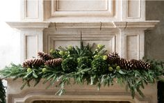 Beautiful mantle with oversized pine cones and fresh greens.