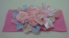 Faixa em meia de seda com bico cambraia flores em fita e laço com detalhes em chatons, para deixar sua linda princesa encantada. R$ 14,90
