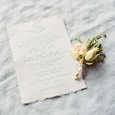 Wedding invitation with pale blue calligraphy on deckle edge paper by Brown Linen Design. Boutonniere by Rosegolden Flowers. Image by Ryan Ray.