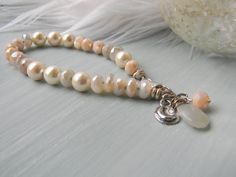 Moonchild  Artisan Gemstone Bracelet   By:  Fire-Imp Lampwork Beads  Soft, feminine colors abound in this beautiful beautiful bracelet. Faceted Moonstone beads sparkle with every movement and subtly shift in color, going from grey to white, peach, and silver. White and champagne shell pearls add to the moonlit glow, along with pale peach Czech beads. Sterling silver artisan moon and stars charms add a touch of rustic whimsy. The entire bracelet is hand knotted and lays beautifully. Sterling…