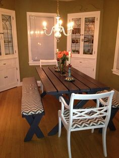 Refurbished from an old/beat-up picnic table to a chic gray dining table with chevron patterned bench and chair covers. Also painted and hung reclaimed chandelier. #cozydining