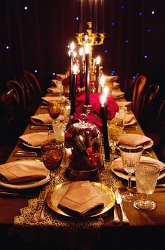 Dark taper candles in varying height break up this glamorous table runner of mixed red roses and gilded votives.