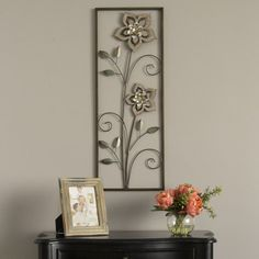 Decorate your walls with the fun Wood Flower Panel Wall Décor. Its natural landscape sets a whimsical element that is timeless. The beautiful mixture of laser cut distressed wood flowers, gold and white metal petals, detailed with a touch of brushed teal finish on each leaf demonstrates its intricate craftsmanship. Product may have some variances in comparison to photo shown.