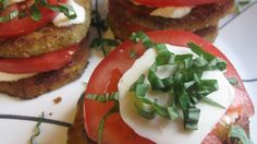 Fried eggplant slices, topped with sliced tomatoes and mozzarella, are ...