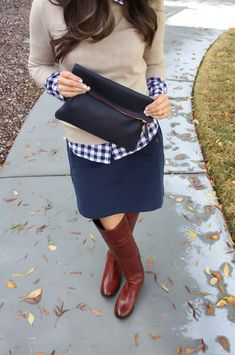 plaid under sweater paired with a skirt and riding boots