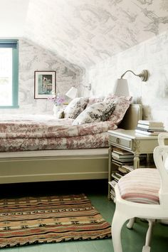 Toile wallpaper and bedding in a light-filled bedroom.