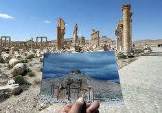 TOPSHOT - A general view taken on March 31, 2016 shows a photographer holding his picture of the Arc du Triomphe (Triumph's Arch) taken on March 14, 2014 in front of the remains of the historic monument after it was destroyed by Islamic State (IS) group jihadists in October 2015 in the ancient Syrian city of Palmyra. Syrian troops backed by Russian forces recaptured Palmyra on March 27, 2016, after a fierce offensive to rescue the city from jihadists who view the UNESCO-listed site's…